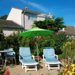 Image of sunbeds, parasol, table and chairs on the patiio